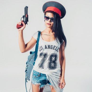 Fashion swag sexy girl holding toy gun woman having fun wearing police cap.