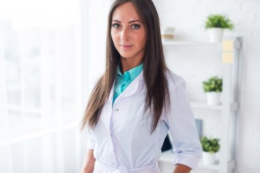 Portrait of young woman doctor with white coat standing in medical office looking at the camera.