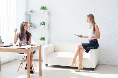 Two young woman colleague at office working and talking