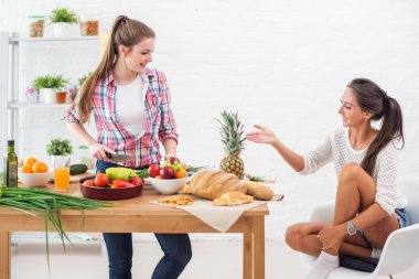 Woman cooking in a kitchen and talking with her friend concept preparing culinary friendship.