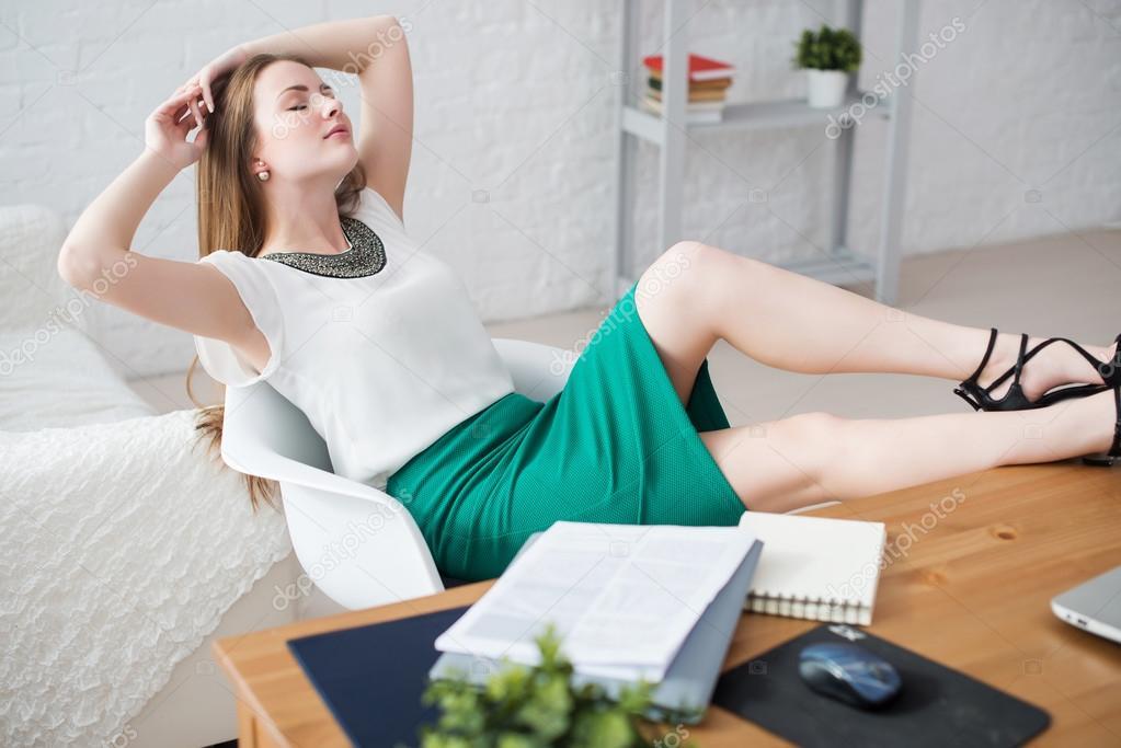 Empresaria descansando las piernas relajantes en las manos de mesa detrás  de su cabeza y sentado en una silla en la oficina — Foto de undrey ddfc0cb838c4