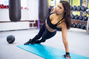 Fit woman doing side plank yoga