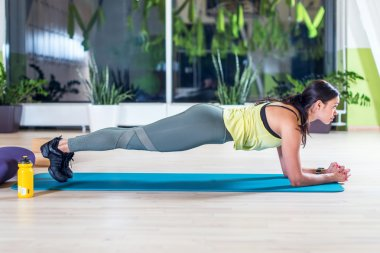 woman doing plank exercise in gym