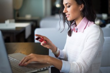 Woman doing online shopping at cafe