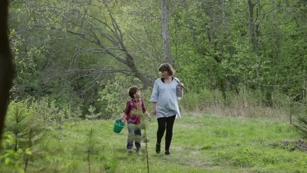 Cute pregnant woman with her six year old son go fishing through the forest
