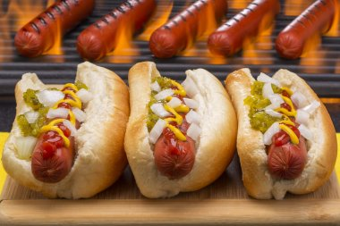 Three Delicious Hot Dogs with Grilling Barbecue Background