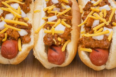 Three delicious chili hot dogs on a wood cutting board