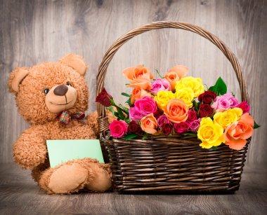 Fresh roses with teddy bear