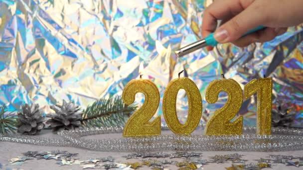 Žena ruka světlo zlaté svíčky 2021, zblízka. Na pozadí jsou stříbrné kužely a větev. Koncept Nového roku a Vánoční svátky.