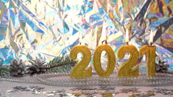 Detailní záběr hořících zlatých svíček2021. Na pozadí jsou stříbrné kužely a větev. Koncept Nového roku a Vánoční svátky.