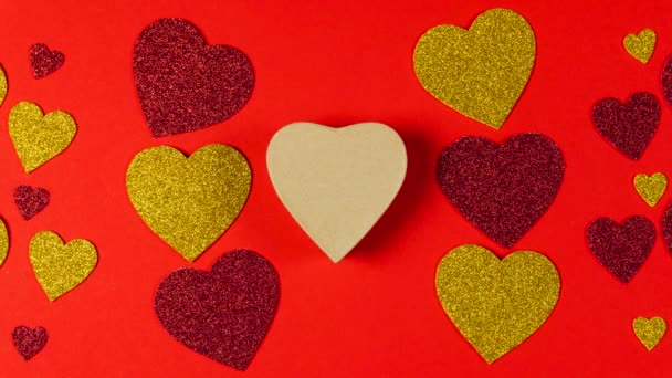 Stop motion animation. The red and golden shiny heart moves to paper gift box in the shape of a heart. Flat lay. Concepts of love symbol, Valentines day, festive and greeting card.
