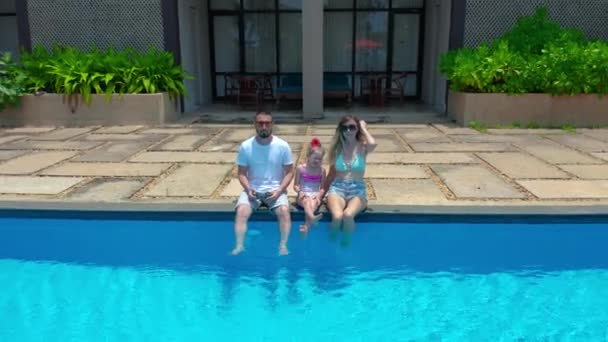 Happy family smiling and looking at camera in swimming pool in Sri-Lanka. Pretty little girl with her parents in swimming pool. Aerial view 4K.