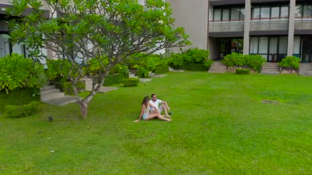 Couple man and woman seat on the grass against the trees in the tropics resort in Sri-Lanka. Aerial view 4K.