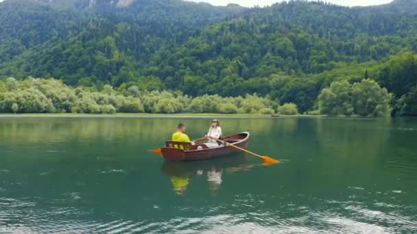 Young couple are sailing on a old wooden boat in Biogradsko Lake in Montenegro. Aerial view 4K.