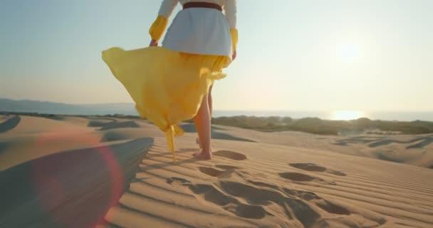 Sexy woman in yellow dress waving by wind in desert. Lady walking on dune