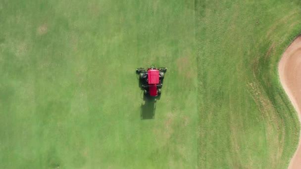 Gardener seká zelenou trávu na perfektním golfovém hřišti. Letecké krásné golfové hřiště 4K