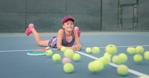 Roztomilé dívka ležící na tenisovém kurtu jako parta tenisových míčků valí směrem k ní
