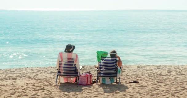 Muž a žena používají lehátka, zatímco sedí u oceánu na pláži
