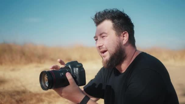 Zpomalený pohyb soustředěný pohledný muž při pohledu do profesionálního okna kamery a na obrazovce