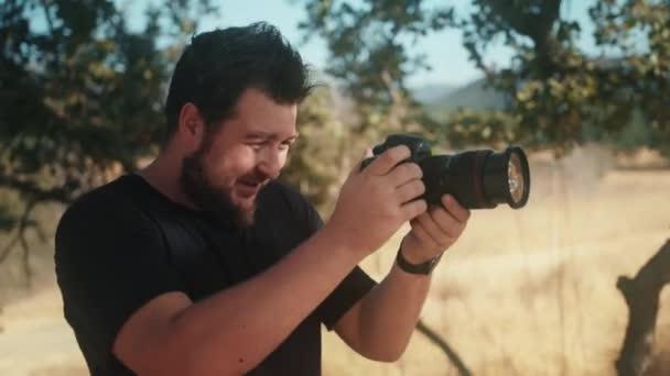 Frontansicht eines professionellen Fotografen, der auf die Kamera blickt und Fotos macht