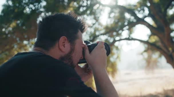Rückenansicht eines professionellen Fotografen beim Fotografieren im Naturpark bei Sonnenuntergang
