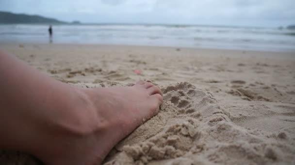 Žena nohy kopání písku na pláži