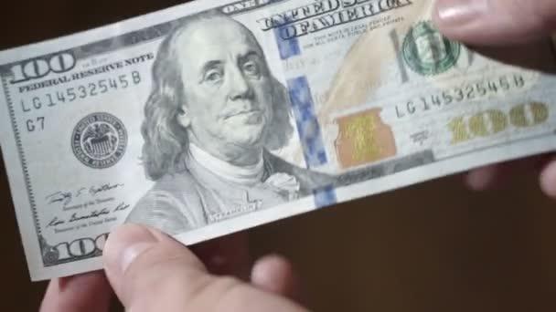 Sto dolarové bankovky v rukou člověka. closeup