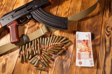 Kalashnikov rifle and Russian rubles on the table