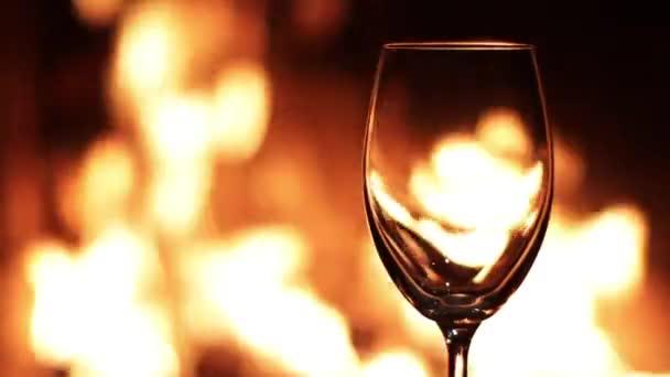 Flammen in einem leeren Glas auf dem Hintergrund des Feuers im Kamin