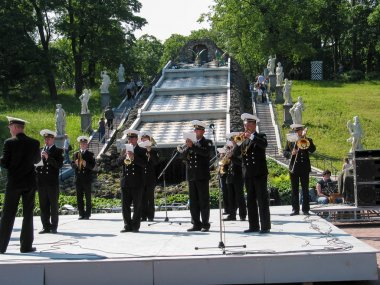 PETERHOF, ST PETERSBURG, RUSSIA - JULY 13, 2003: Russian naval orchestra performs for tourists at formal garden near fountain Cascade Chess Mountain on July 13, 2003 in Peterhof, Russia