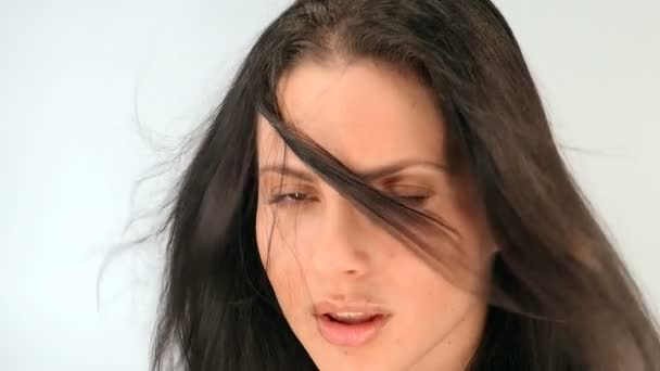 Fiatal gyönyörű lány pózol a stúdióban, lassú mozgás