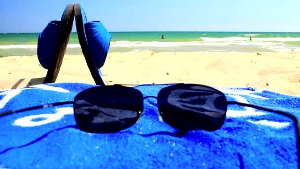 Sluneční brýle a modrý ručník na písečné pláži