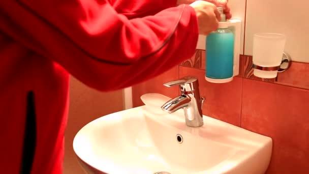Muž myje ruce na umyvadlo v koupelně