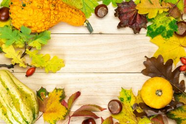 Autumn flat lay. Natural harvest with orange pumpkin, fall dried leaves, red berries and acorns, chestnuts on wooden background in shape frame. Autumn, fall, thanksgiving day concept