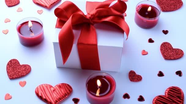Szerelmi háttér: Valentin nap piros szív, romantikus ajándék doboz, gyertya fehér asztalon. Romantikus üzenet sablonja