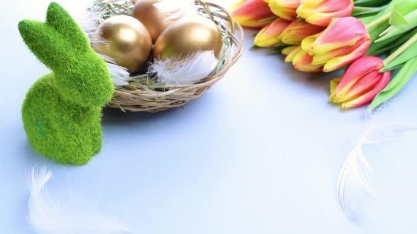 Goldene Ostereier im Korb mit Frühlingstulpen, weiße Federn auf pastellblauem Hintergrund in froher Osterdekoration. Frühjahrsferienkonzept