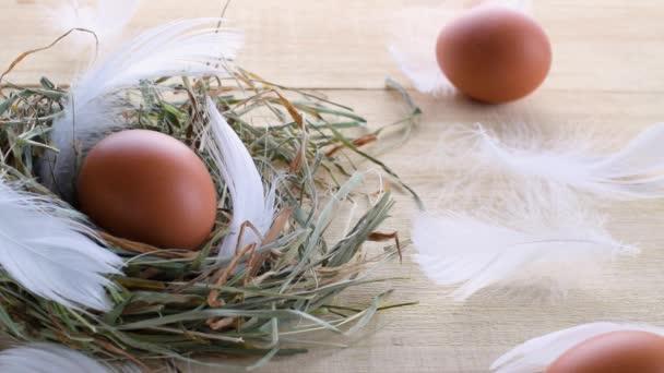 Ostersymbol. Eier in naturfarbenem Korb mit Frühlingstulpen, weiße Federn auf hölzernem Tischhintergrund in froher Osterdekoration. Glückwunsch zum Osterentwurf