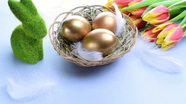 Eierfarbe. Frohe Osterdekoration: goldfarbene Eier im Korb mit Frühlingstulpen, weiße Federn auf pastellblauem Hintergrund. Folie minimalistisches Ei-Design, moderne Vorlage