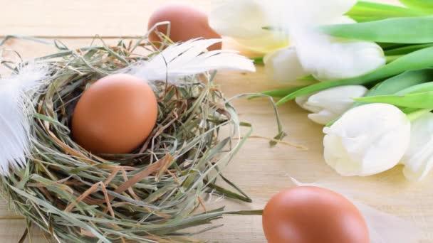 Ostereierkorb. Naturfarbenes Ei im Korb mit Springtulpen, weiße Federn auf hölzernem Tischhintergrund in froher Osterdekoration. Traditionelle Dekoration im Sonnenlicht