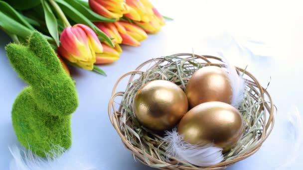 Tojásszín. Kellemes húsvéti dekorációt: arany színű tojás kosárban tavaszi tulipánnal, fehér toll pasztell kék háttérrel. Foil minimalista tojás design, modern sablon