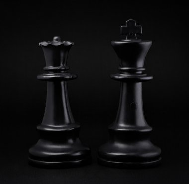 Chess. Black King and Queen on black background. The most powerful figures. Set of chess figures.