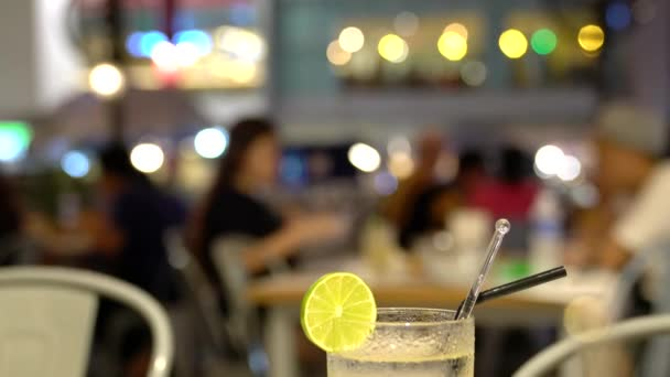Blurred diners in restaurant with bright lights at the background. Defocused restaurant. Focus on a glass of lime juice drink.