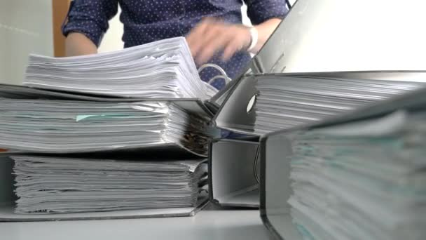 Businesswoman arranging and stacking files on top of each other.