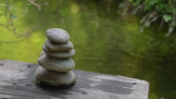Pyramid of pebble stones at pond side with beautiful nature reflection. Zen or wellness concept.