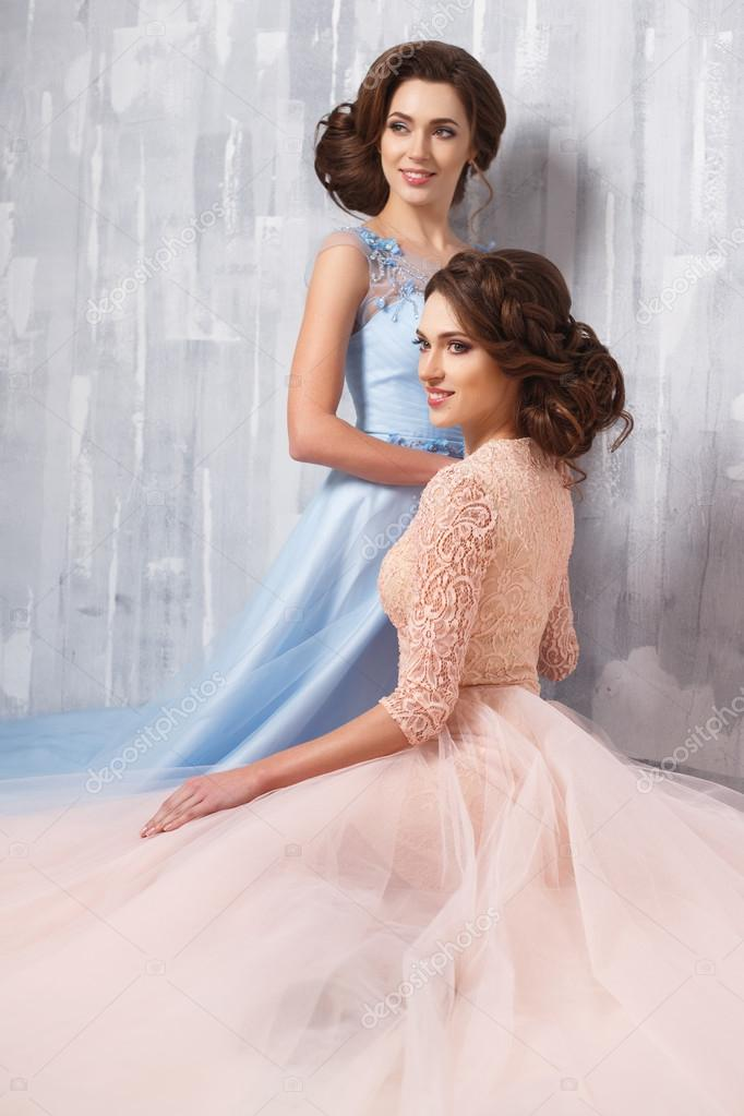 Two Beautiful Twins Young Women In Luxury Dresses Pastel Colors