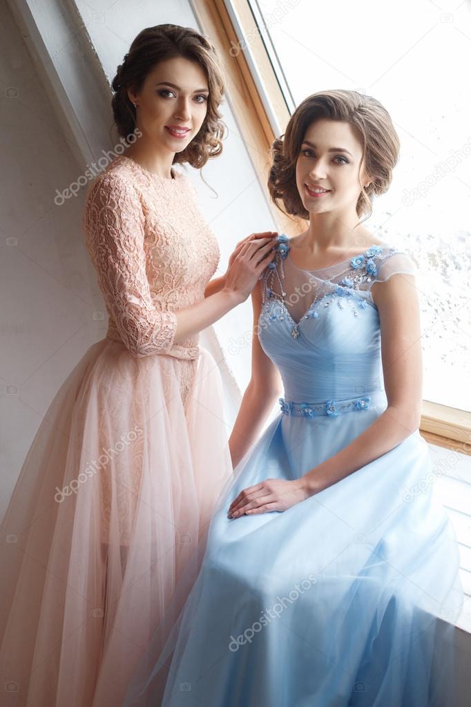 e0177b5dfb34 Δύο όμορφες δίδυμα νεαρών γυναικών σε πολυτελή φορέματα
