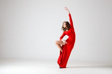 Dancing lady in a red dress. Contemporary modern dance on a white background isolated. Fitness, stretching model