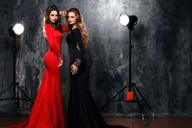 Two sexy elegant women in evening dresses with dramatic makeup and hairstyle, fashion beauty portrait