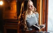 elegante junge Dame mit klassischem Buch im teuren Interieur