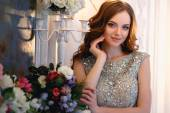 Fotografie Beautiful young lady in a luxury dress in elegant interior with a bouquet of flowers